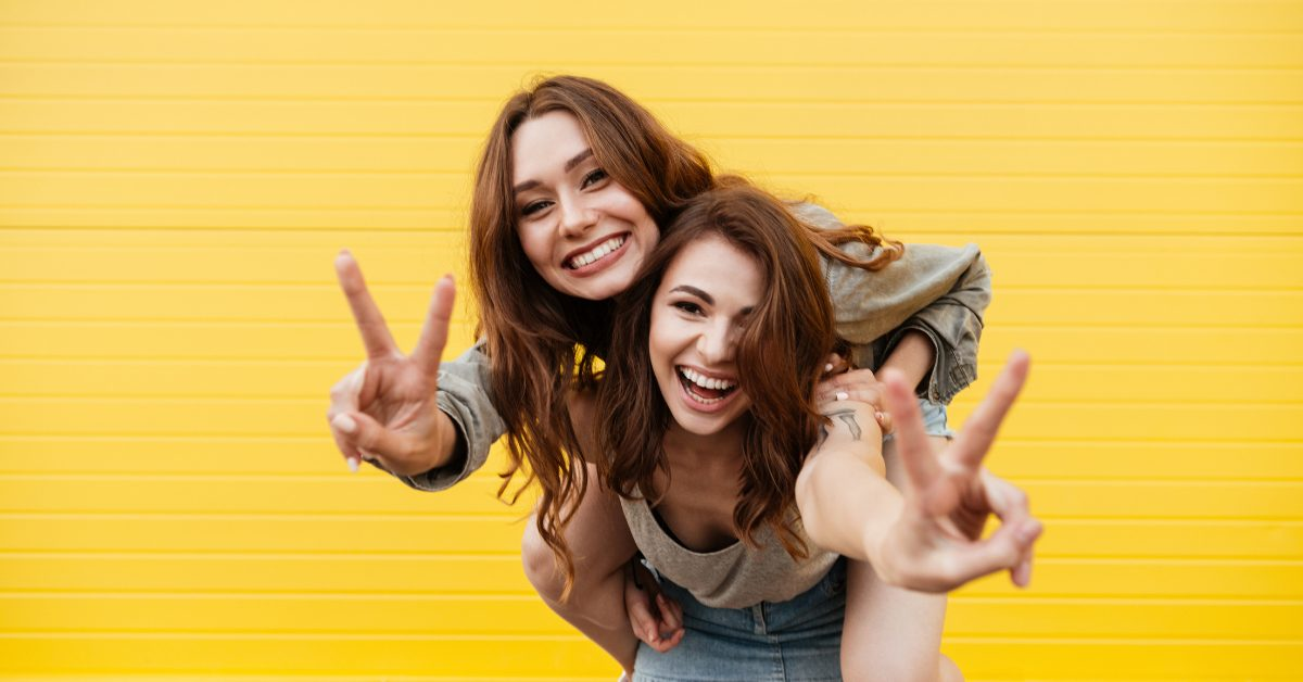 two happy young friends smiling at the camera and making peace signs with their hands